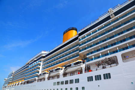 cruiser: Large cruise ship with yellow funnel and blue balcony rise to blue sky