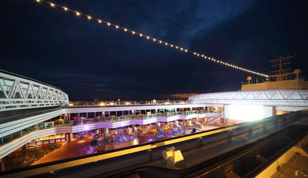 boat party: People enjoy night party on the deck of illuminated cruise ship