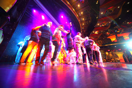 cruise liner: People crowd dance at an illuminated stage of restaurant on cruise ship