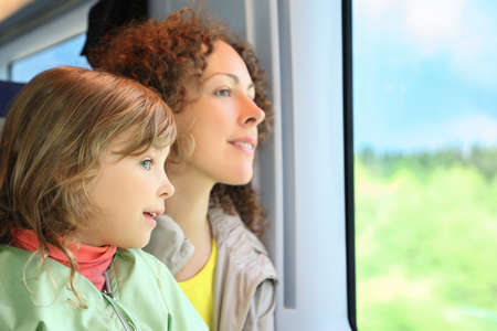 passenger train: Mother with daughter ride in  speed train on rest in  day-time