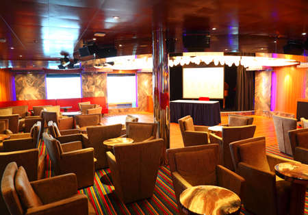 cruise travel: Interior of cafe with stage and armchairs and tables on the cruise ship deck at day