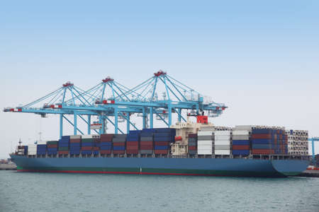 emirates: Big cargo boat docked to industrial port with several blue cranes Editorial
