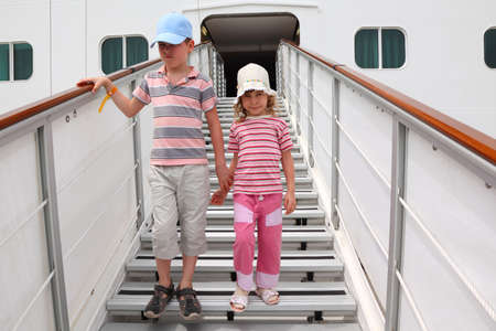 companion: little boy and girl standing on companion ladder on large white passenger liner
