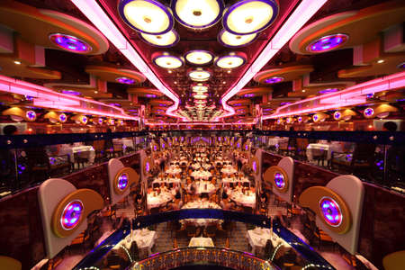dinner cruise: restaurant with modern bright interior, circle lamps and pink light, view from above