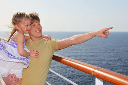 hand rails: father standing on cruise liner deck, carrying his daughter and pointing for finger at right side