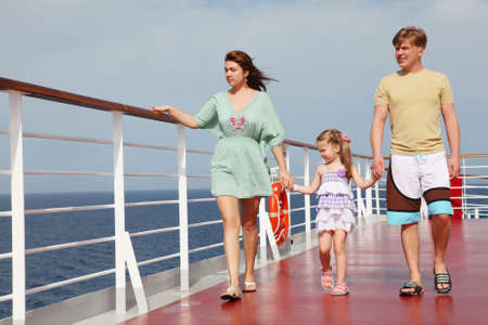 family with daughter walking on cruise liner deck, full body, looking left