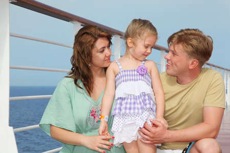 Happy parents with small daughter enjoy sea on yacht photo