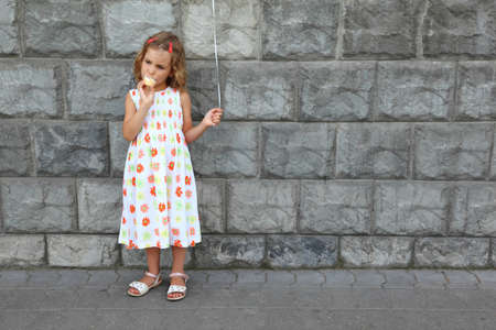girl with gray eyes: Little girl in  white sarafan eats an ice-cream and holds an air marble near  stone wall Stock Photo