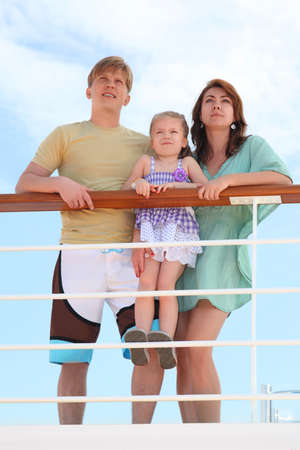 hand rails: family with daughter standing on cruise liner deck near rail, child standing on fence Stock Photo