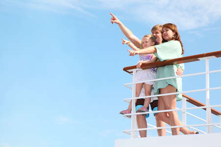 young happy family rests on yacht and indicates something interesting in sea
