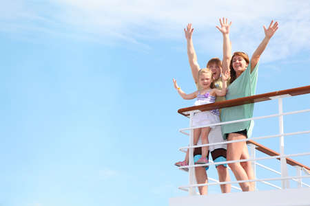 cruise travel: young happy family with little girl with hands uprests on yacht and is glad at life from soul