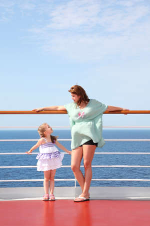 mom and daughter, which very strongly love each other at sea on deck of yacht Standard-Bild