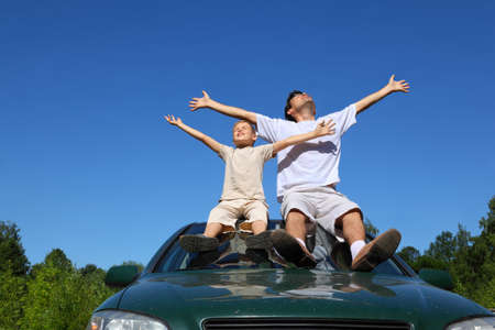 hand lifted: Father with  son sit on  roof of car, lift  person in sky and widely place hands