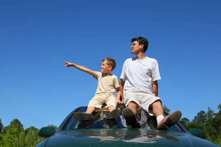 specifies: Father with son of sit on  roof of car in  day-time and look aside which  son specifies hand
