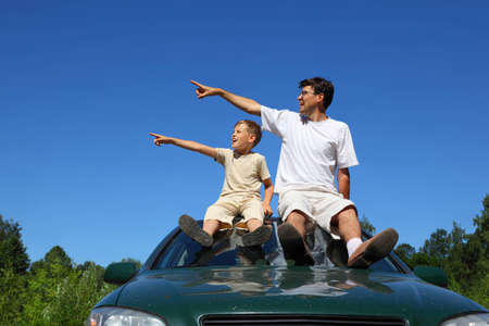 specifies: Father with son  sit on  roof of car in  day-time and look aside in which everybody specifies one-arm