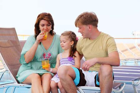 papa y mama: , pap�, mam� e hija descansan en la cubierta del yate y beber jugo sabroso Foto de archivo
