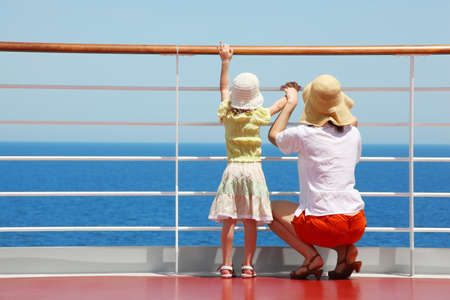 aboard: behind mother and her daughter standing on deck of yacht and they look far aboard