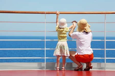 loin: derri�re m�re et sa fille debout sur le pont du yacht et ils chercher bien loin � bord de