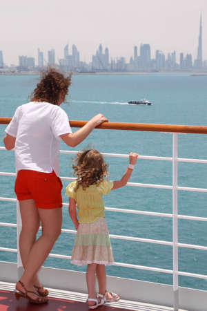 mother and daughter standing near rail on cruise liner deck and looking at boat, view from back, city on horizon