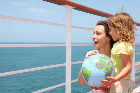 half globe: mother and daughter holding inflatable globe on cruise liner deck, half body