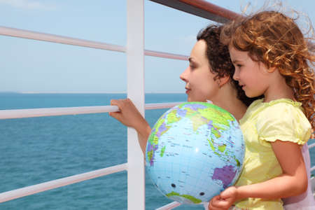 half globe: mother and daughter on cruise liner deck, child holding inflatable globe, half body Stock Photo