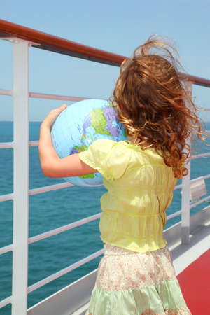 half globe: little girl standing on cruise liner deck and holding inflatable globe, half body, view from back