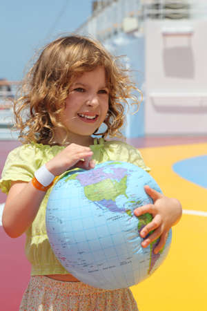 half globe: little girl standing on cruise liner deck and holding inflatable globe, half body Stock Photo