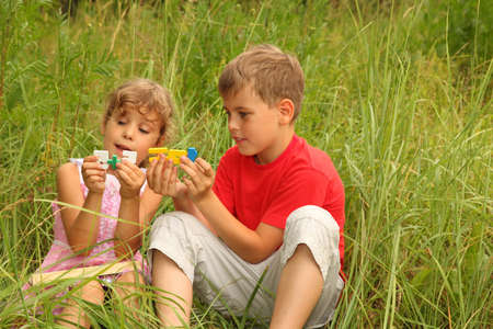 little boy and girl: little brother and sister sitting in tall grass and play with colorful plastic numbers. 5+5 = 10. focus on numbers  Stock Photo