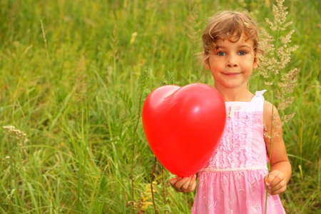 beautiful little girl in pink dress holding red balloon. Girl on nature photo