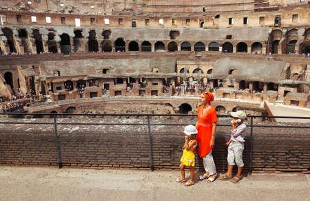 guia de turismo: Madre y sus hijos, hija e hijo, con gu�a electr�nica de pie en el escenario en el Coliseo de Roma, Italia, en d�a soleado