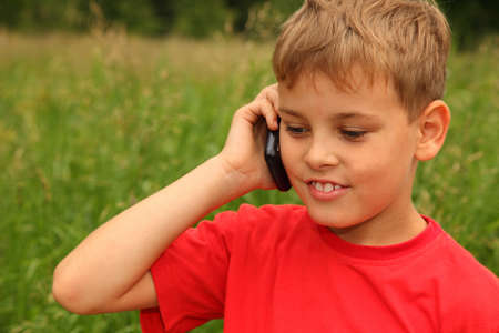 little boy in red shirt talking on cell phone outdoors. Boy smiles Stock Photo - 12647187