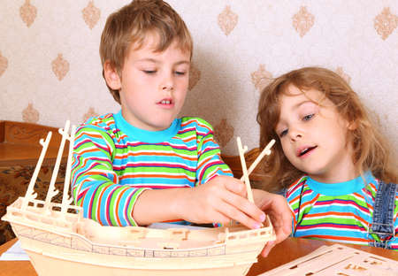 blonde boy: Blonde boy and girl in striped shirt make homemade wooden boat Stock Photo