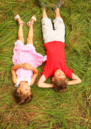 brother in red shirt and sister in pink dress lying on green grass outdoors photo