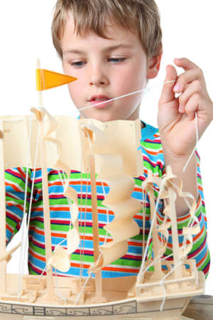 zeal: Small boy in striped shirt works with zeal on artificial ship, he pulls the sail