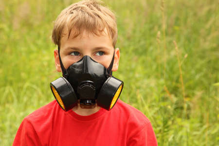 little boy in red shirt with black respirator on face is in nature photo
