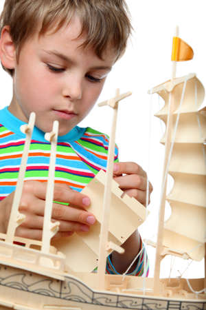 zeal: Small boy in striped shirt works with zeal on artificial ship, he makes sails