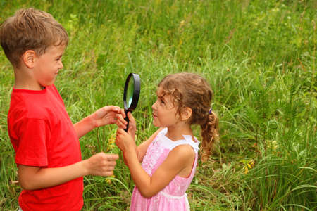 little brother and sister play with big black loop in nature  photo