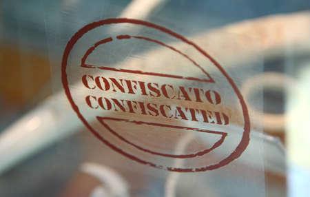 """confiscated: Iscrizione Brown di due parole marrone """"confiscati"""" e """"confiscato"""" su un vetro trasparente, profondit� di messa a fuoco. Archivio Fotografico"""