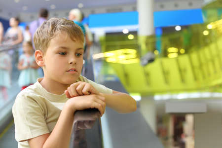 little serious boy standing on escalator and moving up, looking at side Stock Photo - 12640159