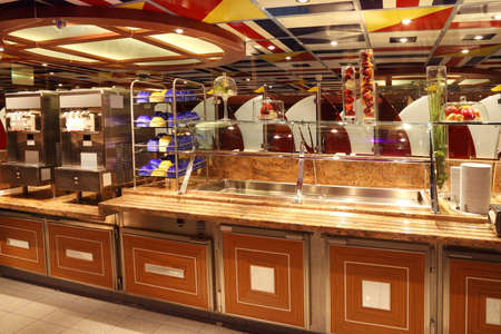 dinner cruise: self-service table with tableware in dinning room on cruise liner Editorial