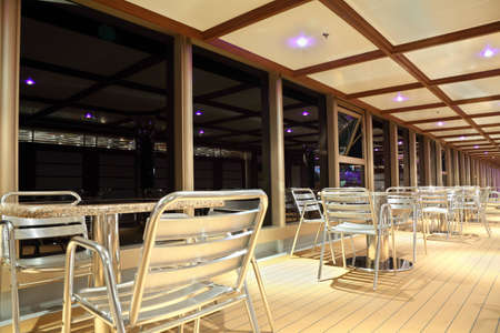 dinner cruise: dinning deck on cruise liner, metal tables and chairs near big window, evening time