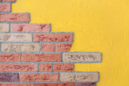 closeup of red brick wall and yellow plaster wall, bright interior photo
