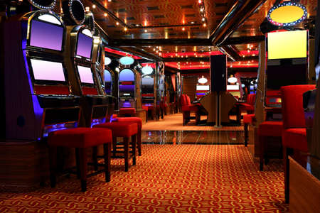 hall monitors: modern empty casino hall with game machines, front view
