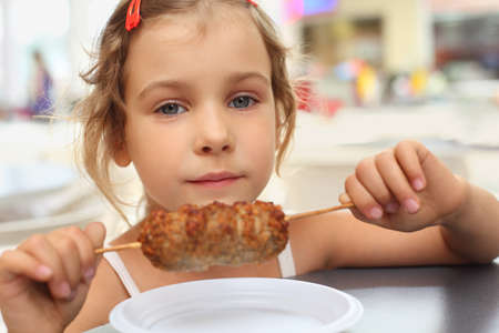 little caucasian girl holding meat on stick, looking at camera photo