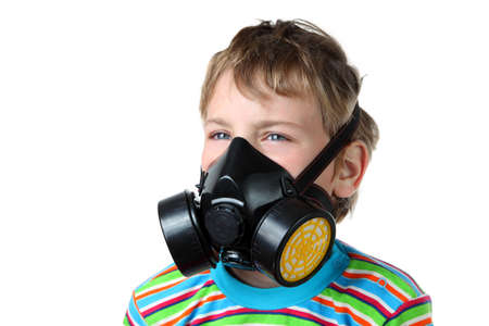 Little blonde boy screws up ones eyes and look toward in black respirator on a white background photo