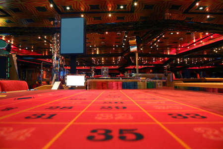 game of chance: room in casino with red table for roulette game, view from table Editorial
