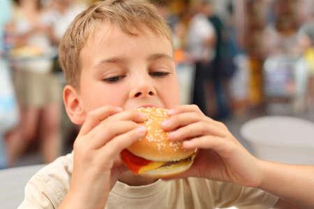 見下ろして、ハンバーガーを食べる小さな白人男の子 写真素材