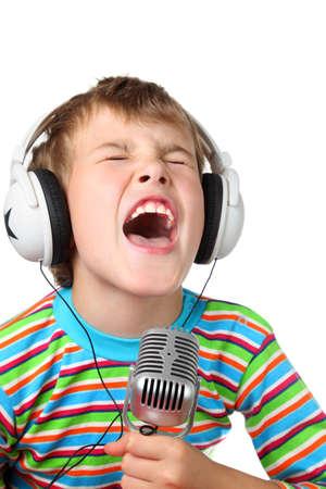 bambini pensierosi: Ragazzino in cuffia con il microfono in mano canta con la bocca spalancata Archivio Fotografico