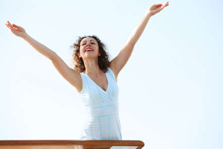 ship deck: young beauty brunette woman standing on cruise liner deck, putting hands up
