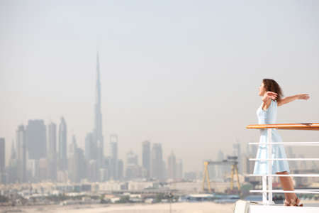 sea side: young beauty brunette woman standing on cruise liner deck, putting hands apart, city on background